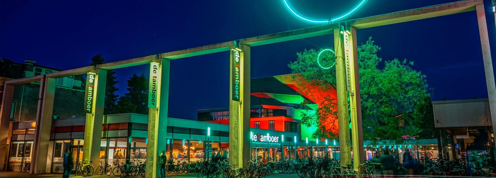 Het gebouw van Theater De Tamboer, gefotografeerd van buiten in de avond.